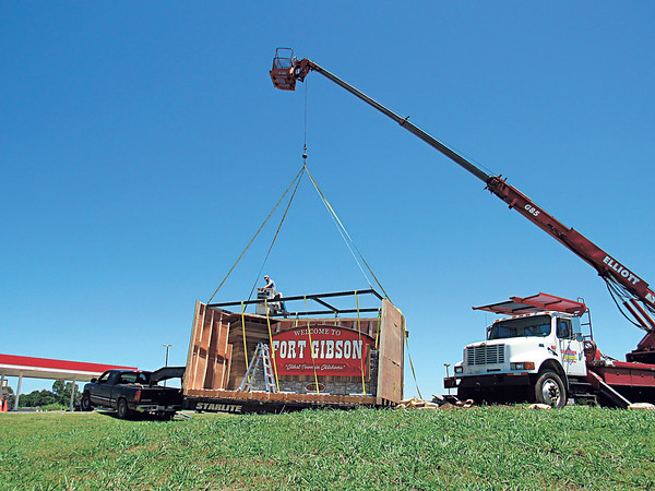 Staff photo by Cathy Spaulding<br /> A Superior Signs crane prepares to lift a Fort Gibson welcome sign out of its crate.