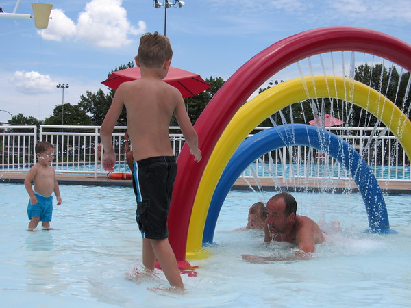 Staff photo by Cathy Spaulding<br /> Rowdy Back, 7, of Oktaha playfully evades his father, Dale Back, who is crawling through a spraying rainbow water feature at Spaulding Park pool Monday afternoon while Levi Hoover, 2, of Muskogee watches the action.