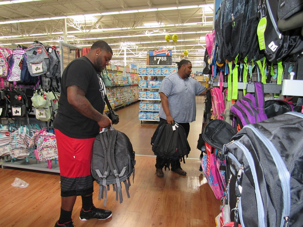 Staff photo by Cathy Spaulding Carolina Panthers nose tackle Robert Thomas and Edward Venters shop for back- packs at Wal-mart. Thomas and other professional football players will hand out backpacks Saturday at an NFL Celebrity Weekend giveaway.