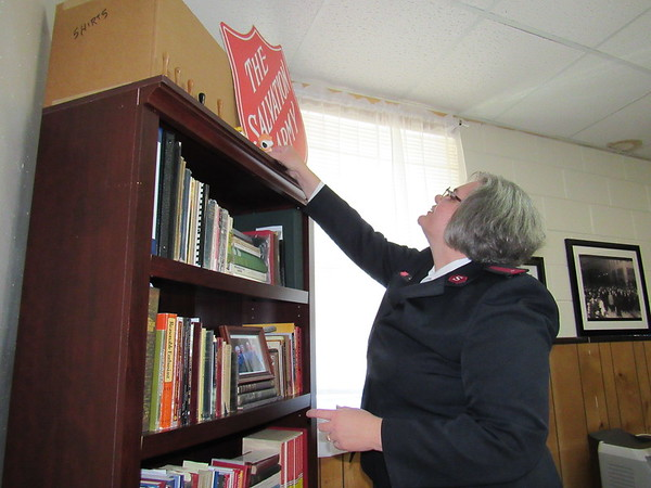 CATHY SPAULDING/Muskogee Phoenix<br /> Lt. Teri Smith adjusts a Salvation Army sign in an office at the Muskogee Salvation Army. She and her husband, Lt. Charles Smith, came to Muskogee last week from El Dorado, Arkansas.