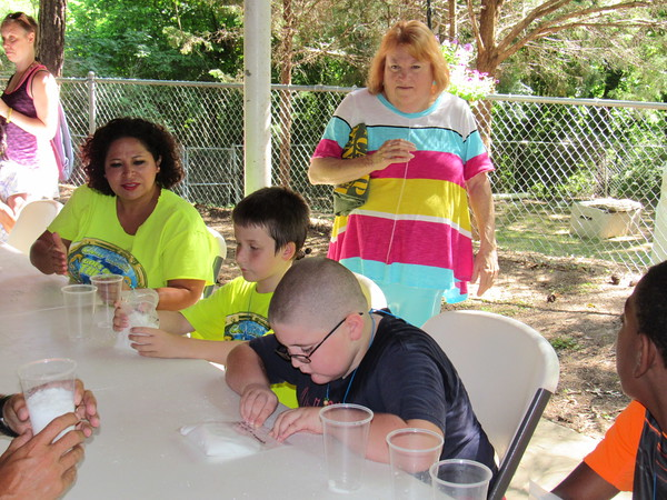 Staff photo by Cathy Spaulding<br /> Retiring Muskogee Public Schools Special Education Director Debbie Winburn, standing, watches Camp Bennett soap-makers, from left, counselor Susan Garland and campers Caleb Crowe, 9, and Antonio Perrotta, 8. Soap-making is one way campers learn the works and wonders of science.