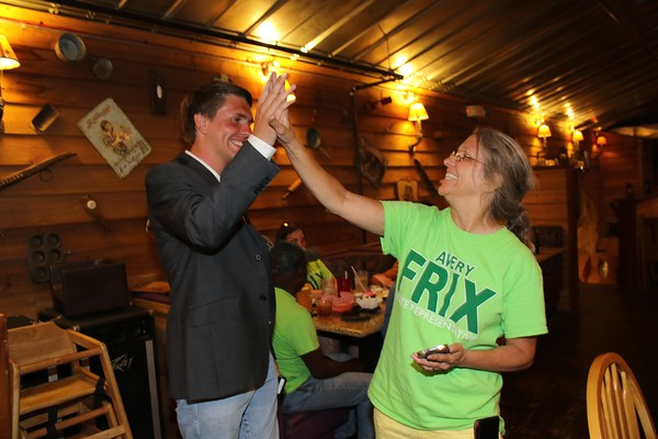 Special photo by John Hasler Avery Frix and his mother, Paige, exchange a high-five at his watch party Tuesday at Okies Restaurant as late results show Frix with a strong lead. He kept the lead, winning the Republican nomination for the House District 13 seat.