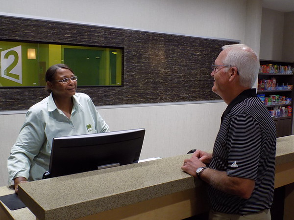 Staff photo by Mike Elswick<br /> Donna Hamilton, customer service representative at Home2 Suites by Hilton in Muskogee, visits with hotel guest Mike Hays of McCook, Nebraska, on Wednesday. The hotel on Military Boulevard is one of several that have opened in the city in the past year or two.