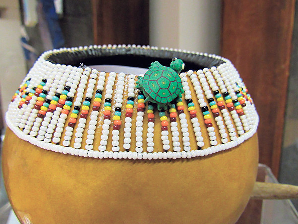 Photo by Cathy Spaulding<br /> A wee ceramic turtle climbs beadwork on a bowl crafted by Choctaw artist Doecha Carolyn Harris. It is one of 25 miniature items on display July 1-31 at Five Civilized Tribes<br /> Museum.