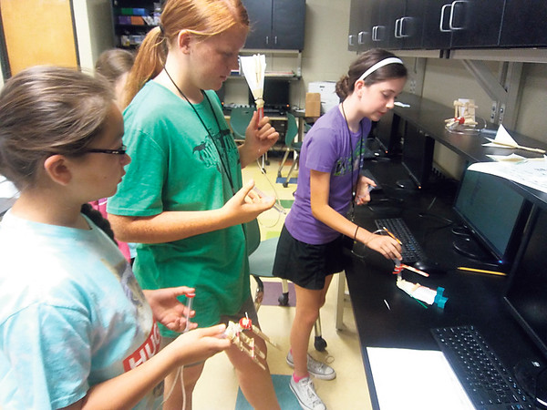 """Staff photo by Wendy Burton<br /> Junior high students Piper Jackson, left, Sieara Collins and Alexandra Locke demonstrate how the """"prosthetic hands"""" work that they built at Muskogee High School's summer engineering camp."""