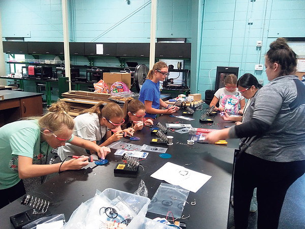 Staff photo by Wendy Burton<br /> Junior high girls learn how to solder resistors on boards at the recent engineering camp held at Muskogee High School's Fab Lab.