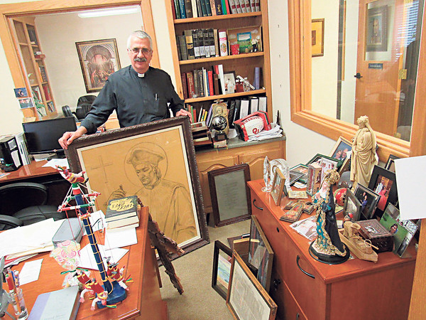 Staff photo by Cathy Spaulding<br /> The Rev. Michael Knipe has kept and collected all sorts of mementos over his six years at St. Joseph Catholic Church. His tenure ends Saturday.