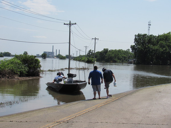 Two men prepare to board a boat to cross water covering Poplar Street west of Fort Gibson. The OG&E electric plant is in the background.