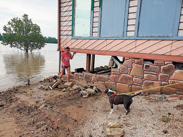 CHESLEY OXENDINE/Muskogee Phoenix<br /> Webbers Falls resident Angela Moore points out where flooding has washed away the foundation of her aunt's restaurant, Theresa's Cafe.