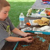 """Staff photo by Mark Hughes<br /> Joel Hall makes a seed bomb using dirt and potting soil mixed with wildflower seeds. """"You throw it on the ground, and it grows,"""" he said. The supplies were in a kids' zone Saturday at the Real Okie Plants and Things festival at the Papilion at Honor Heights Park. Pottery, handmade glasswork and a variety of plants were available for sale."""