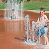 Staff photo by Wendy Burton<br /> Wyatt Hill, 5, plays at the Elliott Park splash pad while brother Ben Hill, 10, sits in a wall of water in the background. The brothers and two other siblings spent the afternoon staying cool at the park Monday. Muskogee's parks with splash pads are located at Honor Heights Park, 1400 Honor Heights Drive; Elliott Park, 840 Altamont St.; Robison Park, 1100 Gulick Ave.; Beckman Park, 1500 W. Broadway; and Rotary Park, Arline and 24th streets. Hours are 9 a.m. to 9 p.m. seven days a week.