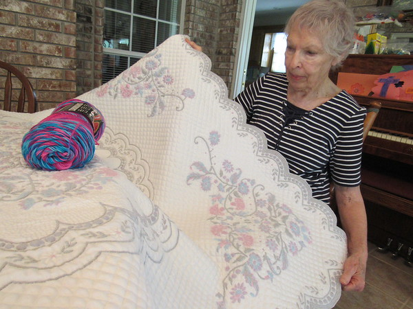 "CATHY SPAULDING/ Muskogee Phoenix<br /> Julianne Nilsson shows her quilt, ""A Study in Shadow Trapunto,"" which won the Muskogee Area Quilter's Guild annual show. She said she's been quilting or sewing since she was 5."