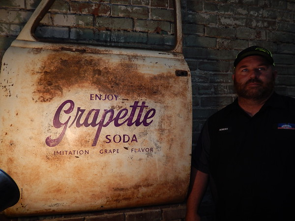 KENTON BROOKS/Muskogee Phoenix<br /> Robert Lawson admires a bottle from his collection as part of his business<br /> that used to be a Grapette Soda bottling company.