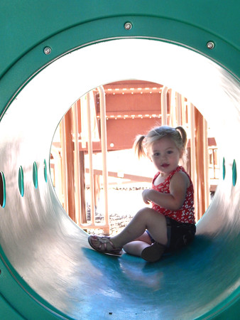 Staff photo by Elizabeth Ridenour<br /> Novalee Phipps, 2, of Locust Grove checks out a play tube Monday af- ternoon at Honor Heights Park's playground.
