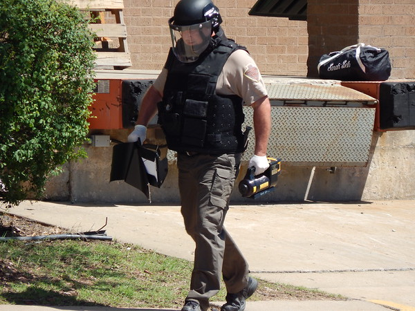 Staff photo by Wendy Burton<br /> Trooper Lon Wise, with the Oklahoma Highway Patrol Bomb Squad, carries equipment back across the street after doing x-rays on a suspicious bag left on the loading dock of the VA Regional Office on the corner of Main Street and Okmulgee Avenue. Muskogee police detained a homeless man shortly after he placed it there Tuesday afternoon and walked away, said Muskogee Officer Lincoln Anderson. The detained man was released from custody as soon as the trooper confirmed there was only clothing in the bag, he said.