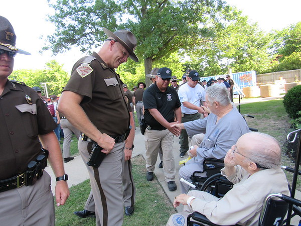 CATHY SPAULDING/ Muskogee Phoenix Trooper Scott King of the Oklahoma Highway Patrol Marine Enforcement Division at Lake Texoma, left, visits with veteran Raymond Browne on Wednesday. King accompanied Cadet Lawmen participants, who visited Jack C. Montgomery VA Medical Center on Wednesday to thank veterans for their service.