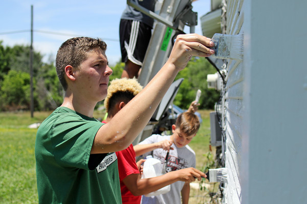 Staff photo by Harrison Grimwood<br /> Cade White, 14, works with a house-painting team on North L Street.