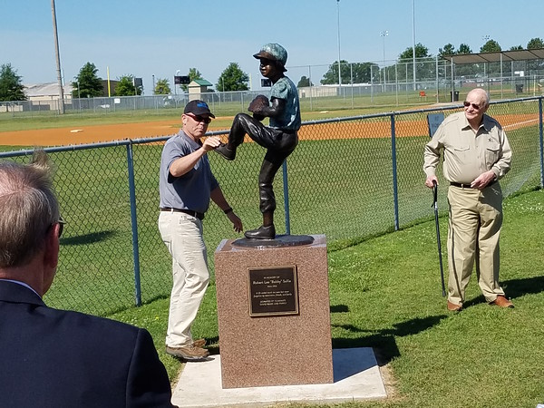 """Staff photo by Mark Hughes<br /> Mark Wilkerson, the director of Muskogee Parks and Recreation, rubs the foot of the statue of Robert Lee """"Bobby"""" Sallie on his way to talk to Marshall Wade. The statue was unveiled Tuesday at Love-Hatbox Sports Complex. Sallie died in 1955 from a line drive to his temple. The Wade family paid for the statue."""