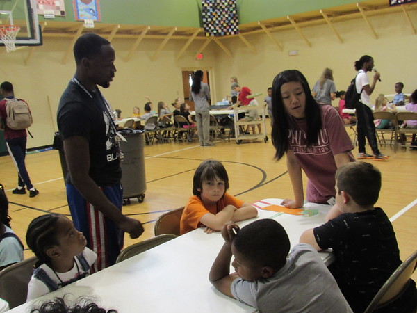 CATHY SPAULDING/ Muskogee Phoenix<br /> AmeriCorps workers Deron Gabriel, left, and Kelly Pan visit with children after a full day of learning and activities at Project Transformation. Six Americorps workers are spending the summer helping with the program.