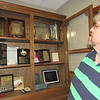 Staff photo by Cathy Spaulding<br /> The Rev. Jason Ravan, pastor of First Baptist Church Webbers Falls, looks through a case displaying memorabilia from the church's 135 years. Items include an early communion plate and a Broadman hymnal.