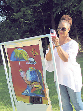 CATHY SPAULDING/Muskogee Phoenix<br /> Denise Hickman of Muskogee Parks and Recreation Department attaches an small American flag to one of the banners up for auction at Symphony in the Park. Banners were painted by area artists.