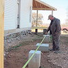 CATHY SPAULDING/Muskogee Phoenix<br /> Eric Trapp of PH Log Homes measures from a porch to a concrete piling. The pilings will support a wing to be added to the Fort Gibson Historic Site's old hospital.