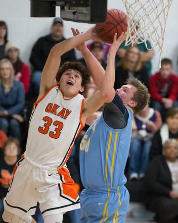 Special photo by Von Castor<br /> Okay's Austin Skiles gets his shot off past Oktaha's Dru Midway during the Mustangs' 84-45 win over the Tigers in January. Okay, the No. 2 team in Class A, squares off against Velma-Alma at 3:30 p.m. Thursday at State Fair Arena in Oklahoma City in the state tournament quarterfinals.