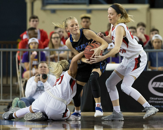 Phoenix special photo by Von Castor<br /> Fort Gibson's Cailey Cunningham, left, and Ali Christie, right, tie up Newcastle's Morgan Bergt for a turnover during Thursday's Class 4A girls state tournament quarterfinal at State Fair Arena in Oklahoma City.