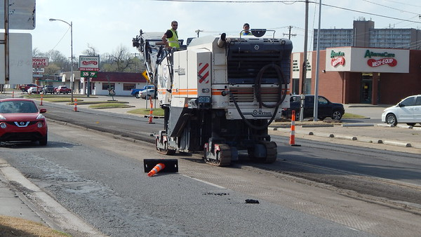 Staff photo by Mark Hughes<br /> Workers from Glover and Associates remove 2 1/2 inches of old asphalt Thursday as part of preparation for laying new asphalt. The work began Tuesday at West Okmulgee Avenue and 32nd Street heading west on Okmulgee, ending just past North 66th Street. The project will cost $1.5 million.