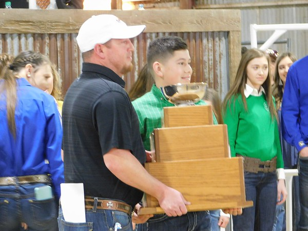 CHESLEY OXENDINE/Muskogee Phoenix<br /> (From left) Steven Maddox and son Maddux Shelby, of Webbers Falls, accept an award for Maddux's grand champion hog at Saturday night's Premium Auction at Hatbox Hangar. Steven was asked to join Maddux owing to a family history of participating in the Muskogee Regional Junior Livestock Show.
