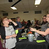 Staff photo by Cathy Spaulding<br /> Cynthia Sanders of Fort Smith, Arkansas, left, samples a wine from the StableRidge Winery table at the Bedouin Shrine's Flying Fez Wine Tasting festival on Saturday. Amy Miller of StableRidge, right, served the sample.