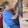 Phyllis Marble holds her canvas up during a Nancy's Paint Pallette class. She said it gives her a better handle on what she's painting.