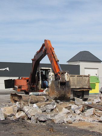 CATHY SPAULDING/Muskogee Phoenix<br /> An excavator scoops concrete chunks during the demolition of a former Shell station Monday. Demolition of the former gas station is the latest part of renovations at Shawnee Crossing shopping center at the corner of York Street and Shawnee Bypass. A former hotel, which later was used for Bacone College housing, was demolished recently.