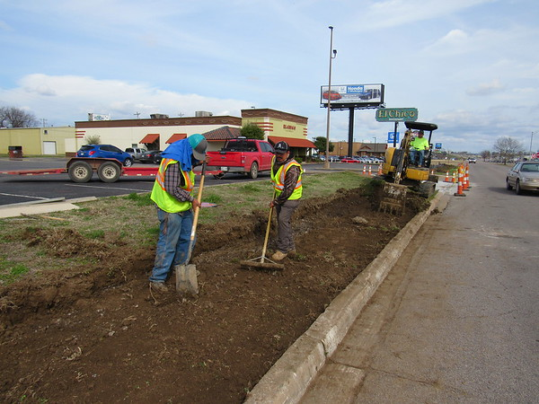 CATHY SPAULDING/Muskogee Phoenix<br /> Ruben Sanchez, left, and Rogelio A. Hormirano shovel and rake dirt while Terry Abell operates a trackhoe to move dirt for a new sidewalk. Crews were constructing sidewalks along the Shawnee Bypass north access road, east of Chicago Street on Wednesday afternoon.