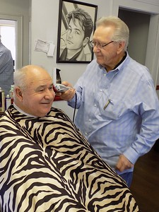 """Staff photo by Mike Elswick Eugene Meeks, in barber chair, said in addition to getting his hair cut by barber J.W. Langton, the regular visits over more than 40 years makes him feel good. """"I'm always happy when I leave here,"""" Meeks said."""