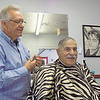 Staff photo by Mike Elswick<br /> Longtime Muskogee barber J.W. Langton works on trimming the hair on Bill Kilpatrick's head recently. Kilpatrick said Langton has been cutting his hair for decades. He said Langton always has stories to tell and is entertaining.
