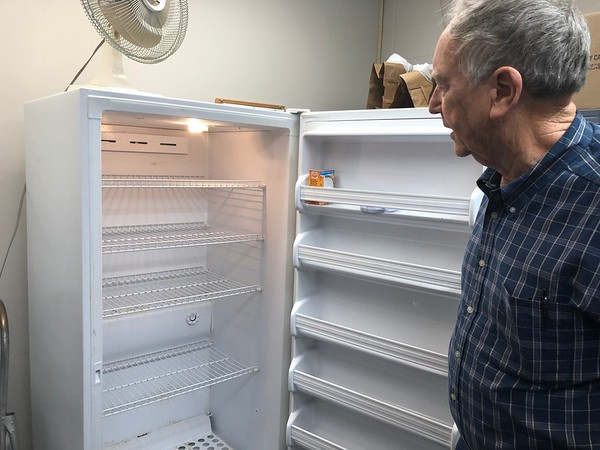 CHESLEY OXENDINE/Muskogee Phoenix<br /> Muskogee Community Food Pantry coordinator Tom Carment inspects an empty meat freezer.