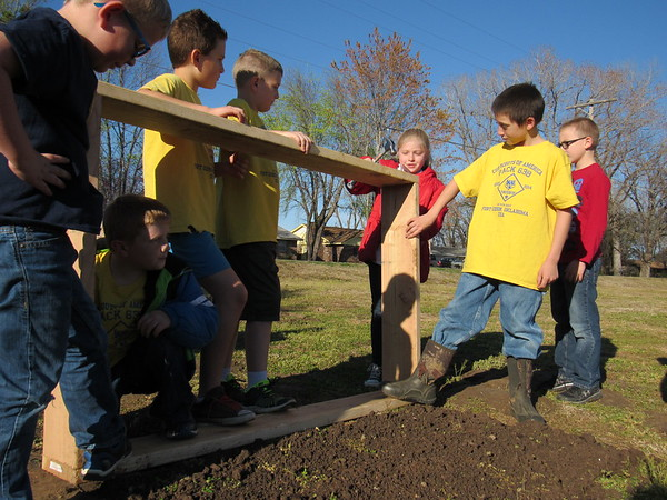 Staff photo by Cathy Spaulding<br /> Girl Scout Rylea Mendenhall, third from right, hammers a garden frame with bracing assistance by Cub Scouts, from left, Jacob Shunkwiler, Wyett Mendenhall, James Reed, Cash Sparks, and from right, Daxton Thomas and Brayden Ellis. The scout groups are building community gardens near Q. B. Boydstun Library.