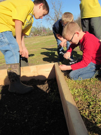 Staff photo by Cathy Spaulding<br /> Cub Scout Brayden Ellis, left, watches fellow scout Daxton Thomas Hammer a community garden frame.