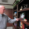 CATHY SPAULDING/Muskogee Phoenix<br /> Retiring Firstar Bank CEO Chris Condley shows a picture of his youngest grandchild, Stella, and a wooden train she made. Family pictures fill his office bookshelf.