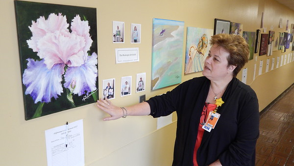 Staff photo by Mark Hughes<br /> Jeri Meier, director of behavioral health at EASTAR Health System, comments on an acrylic painting of an iris located in the hallway going to the cafeteria. Around 24 paintings are up for silent auction until 1 p.m. Friday for the fight against Alzheimer's disease. EASTAR is hosting a free public conference on the subject from 8 a.m. to 3:45 p.m. Friday. A free lunch will be served, and registration is necessary at (918) 429-9436 or at evelyn.gulley@capellahealth.com.