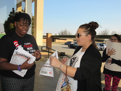 Staff photo by Cathy Spaulding Ben Franklin Science Academy teacher Sharica Cole, left, gives an Oklahoma Education Association information sheet to Ivy Skinner before a Muskogee Education Association town hall meeting, held Thursday at Muskogee High School.