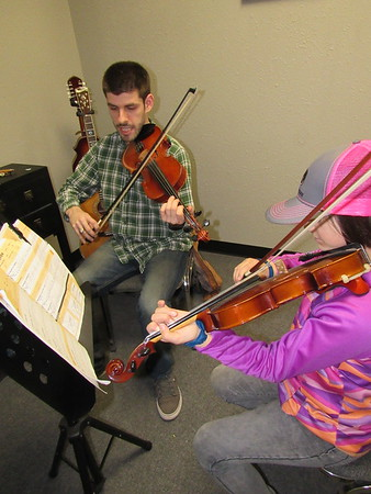 Halston Williams, left, goes over a measure-by-measure fiddle lesson with pupil Eden Perry. Williams has played fiddle since age 9.