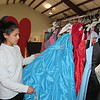 Staff photo by Cathy Spaulding<br /> Salvation Army volunteer Ana Paige pulls a sky blue gown available for high school girls needing help with prom wear. Salvation Army of Muskogee seeks to help girls look good through Project Bibidi Babidi Prom.
