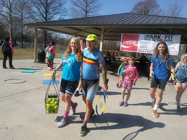 Special photo by Wendy Burton<br /> Ronald and Tiffany Milligan, center, with Muskogee Area Cycling, lead the charge to the tennis courts at Honor Heights during the first session of P.E. in the Park on Saturday.