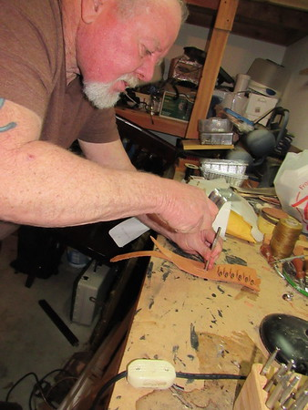 Staff photo by Cathy Spaulding<br /> Gary Babb hammers into a leather holster he's crafting. He said he got involved in leather craft as a youth.