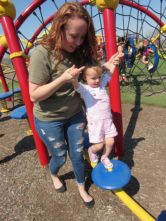 CATHY SPAULDING/Muskogee Phoenix<br /> Lillian Joice helps her 18-month-old daughter Maddie Joice cross steps on a Civitan Park playground set Monday. Spring weather and spring break filled area parks on Monday and Civitan Park was no exception.