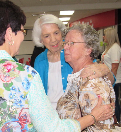 Staff photo by Cathy Spaulding<br /> Retired Fort Gibson teacher's aide Helen Cooper, right, gets a hug from Betty Martin during a chat with Fort Gibson Chamber of Commerce Executive Director Sue Godwin. The three were at the annual Golden Agers' Breakfast at the school cafeteria.