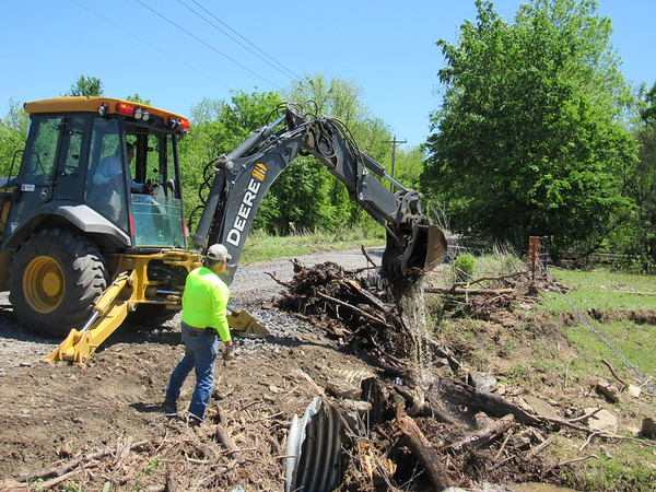 Staff photo by Cathy Spaulding<br /> Muskogee County backhoe operator Ray Fuentez lifts debris from a pipe under Smith Ferry Road on Monday while worker Steve Berryhill observes. Debris had clogged the pipe, causing the road to flood over the weekend.