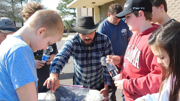 KENTON BROOKS/Muskogee Phoenix<br /> Josiah Parrish, a hobbyist-survivalist from Oklahoma City, opens a bag of charcoal for students to use as he teaches them how to make a water filtration system using a plastic bottle, cotton balls, gravel and charcoal. Parrish taught the survival class Tuesday at the public library. The students learning were, from left, John Cook, Conner Freeman and Nya Olson.